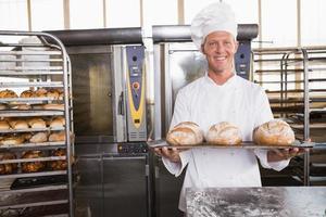 feliz panadero mostrando bandeja de pan fresco foto