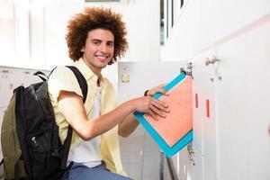 Casual young man shelving folders photo