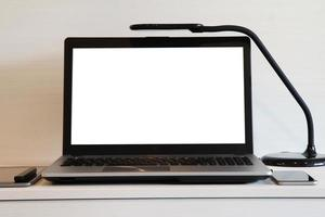 blank screen laptop computer with table lamp