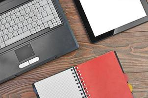 Laptop and office supplies on wooden table photo