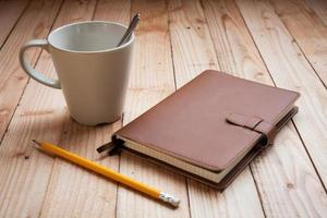 Coffee cup with notebook and pencil photo