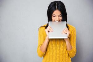 Angry woman biting tablet computer