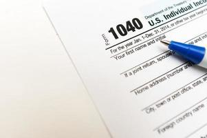 Formulario de declaración de impuestos individual 1040 cerrado con pluma aislada foto