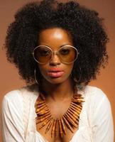Retro 70s fashion black woman with sunglasses and white shirt.
