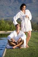 Pareja joven vistiendo batas blancas al aire libre junto a la piscina, sonriendo