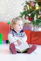 Beautiful little toddler girl reading book under decorated Christmas tree