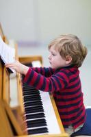 twee jaar oude peuterjongen die piano speelt