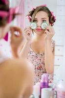 mujer joven en bata de baño con pepino en los ojos foto