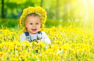 happy baby girl in wreath on  meadow with yellow flowers