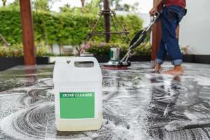 Thaise mensen die zwarte granietvloer met machine en chemic schoonmaken