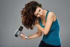mujer con secador de pelo, foto de estudio