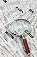 Classified Ad and magnifying glass photo