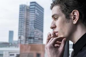 contemplating man at window photo