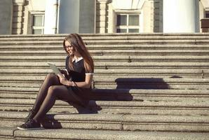 Young student girl sitting outdoor on the steps of University