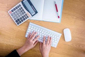 manos femeninas trabajando en un teclado, computadora y papelería