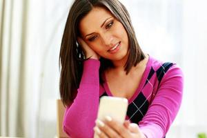 Middle-aged thoughtful woman holding smartphone photo
