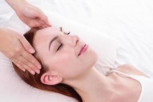 mujer joven disfruta de masaje facial