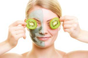 Mujer con máscara facial de arcilla que cubre los ojos con kiwi foto