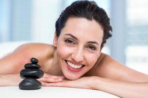 Morena sonriente descansando en una mesa de masaje foto