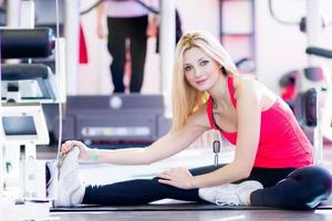 Fit woman stretching her leg to warm up photo