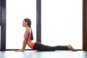 Woman doing yoga exercises in fitness gym photo