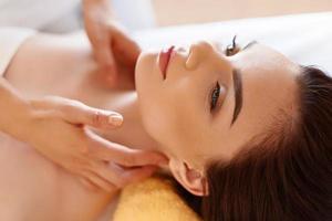 masaje spa Hermosa mujer recibe tratamiento de spa en el salón. foto