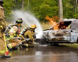 dois bombeiros pulverizando um carro em chamas.