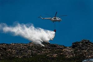 Fire fighting Helicopter drops water load on mountain top.