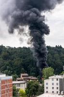 Column of black smoke rising above residential buildings. photo