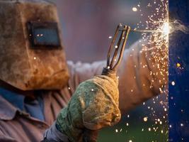 Arc welder worker in protective mask welding metal construction photo