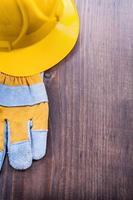 Guante y casco sobre tabla de madera vintage con copyspace construc