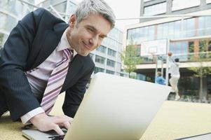 Alemania, Hamburgo, hombre de negocios sentado en el piso usando laptop foto