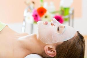 Wellness - woman getting face mask in spa photo