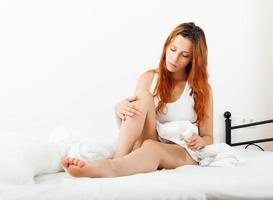 girl applying cream on legs photo
