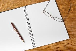 Open notebook with pen and glasses photo