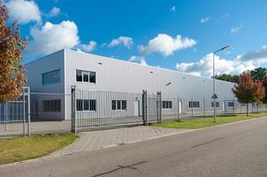 Industrial building fenced off underneath cloudy blue sky photo
