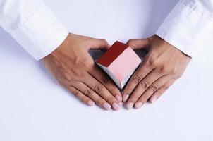mano con forma de corazón y papel de casa foto