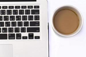 sobre la computadora portátil, una taza de café foto