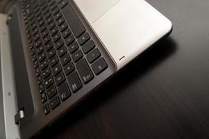 Silver laptop computer with black keyboard close up on desk