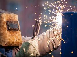 Arc welder worker in protective mask welding metal construction photo
