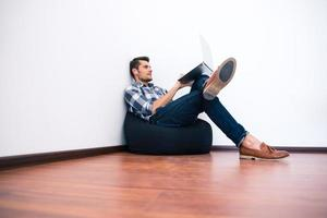 joven en ropa casual usando laptop en bolsa silla foto