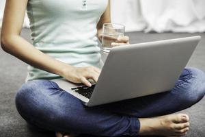 mujer joven sentada mientras usa la computadora portátil