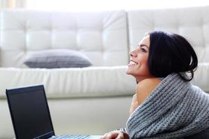 mujer feliz pensativa tirado en el piso con laptop