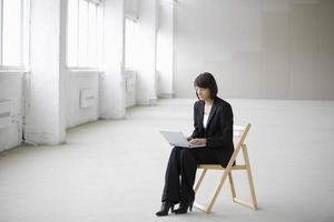 Empresaria usando laptop mientras está sentado en una silla en el almacén
