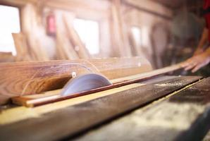 Carpenter sawing wooden planks photo