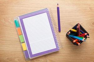 mesa de oficina con bloc de notas en blanco y lápices de colores