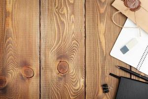 Wooden table with notepad and vintage envelope photo