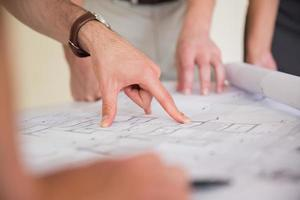 Businessman pointing on blueprint photo