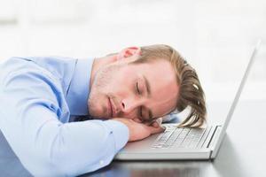 uomo d'affari che dorme sul suo computer portatile
