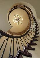 Skyward View of a Spiral Staircase and Chandelier